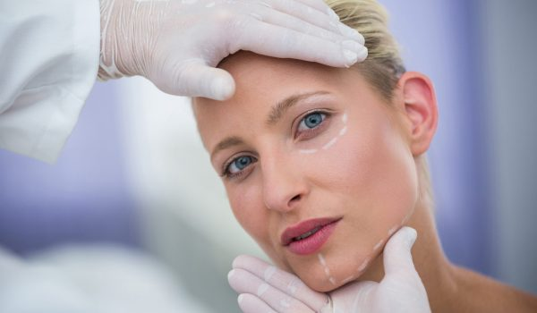 Close-up of doctor examining female patients face for cosmetic treatment