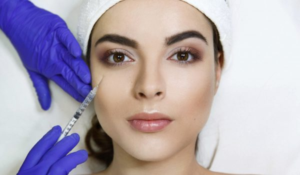 Cosmetologiest makes beauty injection in woman's face in the clinic