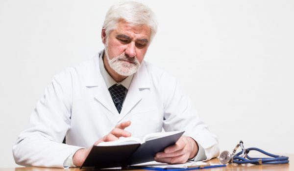 middle aged doctor with gray hair and beard reading his notes
